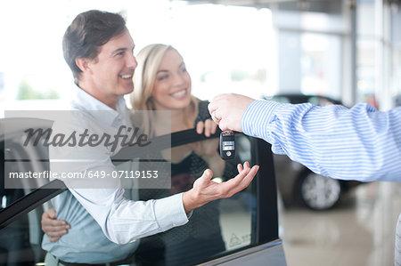 Car salesman handing key to couple in showroom