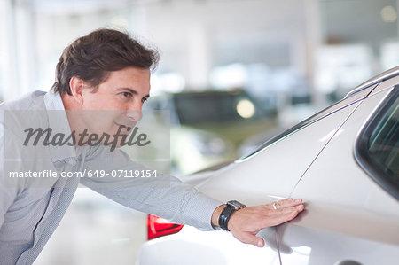 Mid adult man examining car in showroom