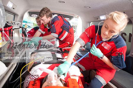 Paramedics using stethoscope on patient in ambulance