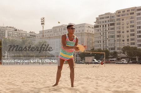 Young man about to hit ball with bat on Copacabana Beach, Rio de Janeiro, Brazil