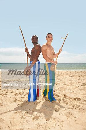Men with berimbau on beach