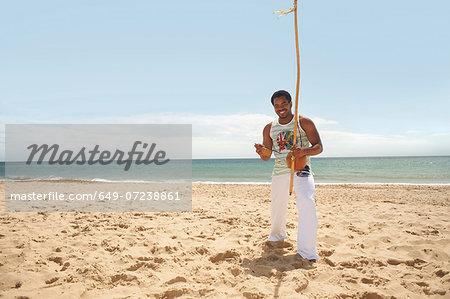 Man with berimbau on beach