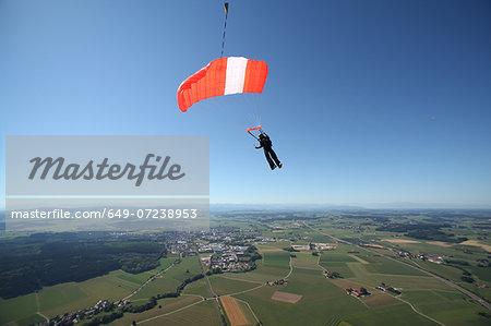 Skydiver parachuting down above Leutkirch, Bavaria, Germany