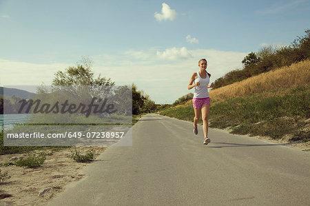 Young female jogger running along riverside