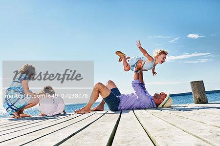 Family playing on jetty, Utvalnas, Gavle, Sweden