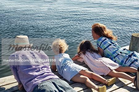 Parents and daughters lying on pier, Utvalnas, Gavle, Sweden