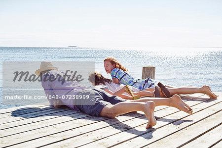 Family lying on pier, Utvalnas, Gavle, Sweden