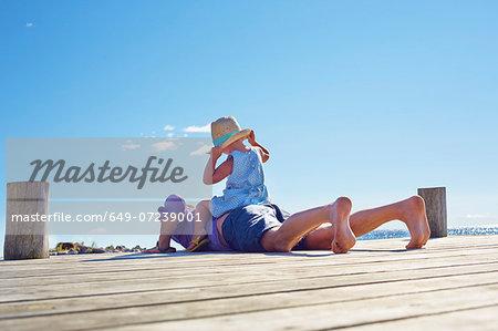 Female toddler and father on jetty, Utvalnas, Gavle, Sweden