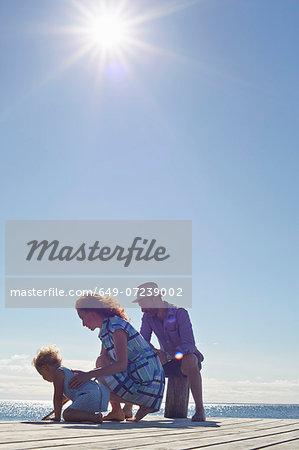 Female toddler and parents kneeling on pier, Utvalnas, Gavle, Sweden