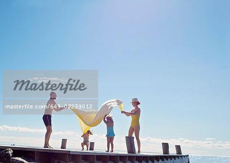 Young family having fun on pier, Utvalnas, Gavle, Sweden