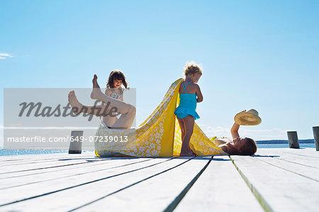Young family fooling around on pier, Utvalnas, Gavle, Sweden