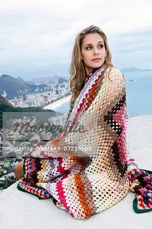 Young woman wrapped in wool blanket, Casa Alto Vidigal, Rio De Janeiro, Brazil