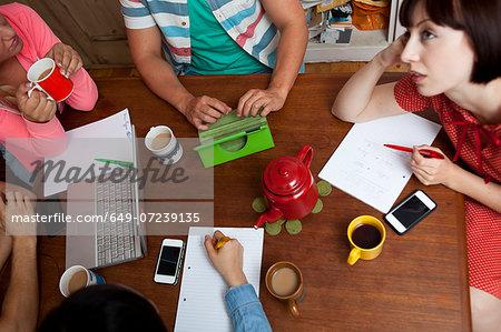 Flatmates brainstorming around kitchen table