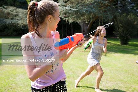 Two teenage girls playing with water guns in garden