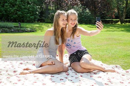 Two teenage girls on picnic blanket taking self portrait