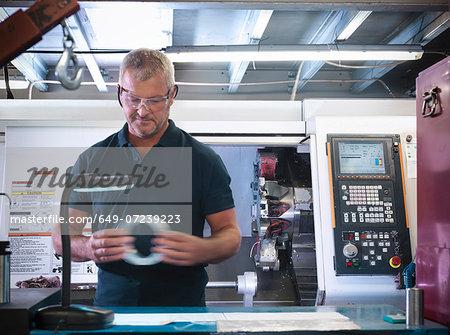 Engineer inspecting metal part in factory