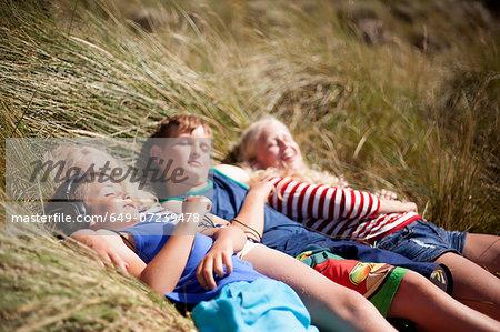 Four friends relaxing in dunes, Wales, UK