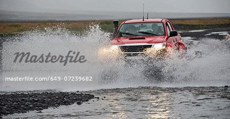 Customised SUV driving through river, Thorsmork, Iceland