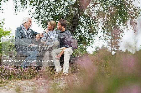 Senior man and mid adult couple sitting on log