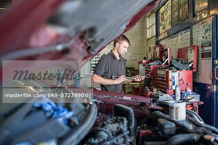 Mechanic holding tool in garage