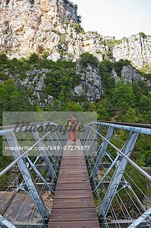 Hiker on hanging footbridge over the Verdon canyon, Provence, France