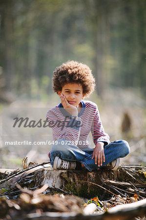 Portrait of boy sitting cross legged on tree stump