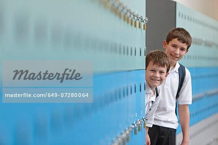 Portrait of two schoolboys behind lockers
