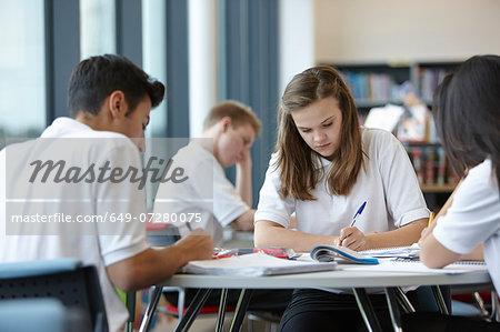 Group of teenagers working in school class