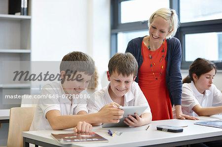 Schoolchildren working in class with teacher