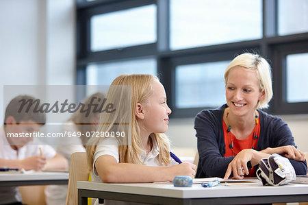 Teacher working with schoolgirl in classroom