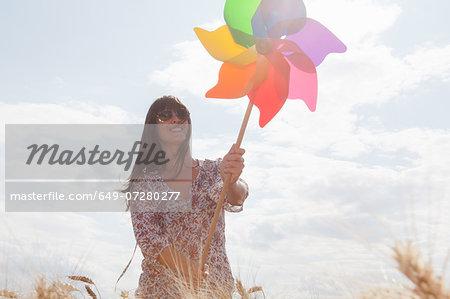 Mid adult woman holding windmill