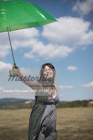 Mid adult woman holding green umbrella