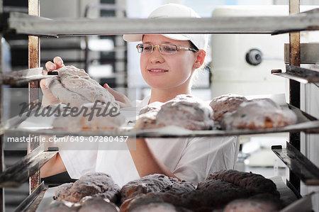 Baker putting bread dough on baking sheet