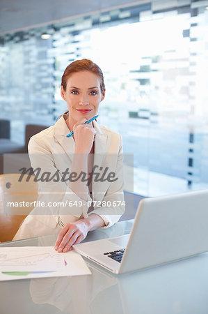 Businesswoman sitting at desk, writing activity