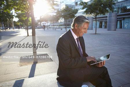 Businessman sitting outside using digital tablet