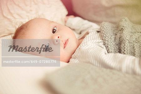 Two month old baby boy lying awake in crib