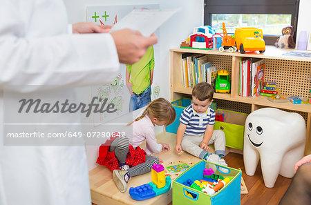 Children playing on floor, dentist in foreground
