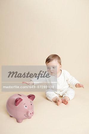 Studio portrait of baby girl reaching for piggy bank