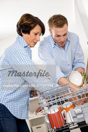 Grandmother and adult grandson emptying dishwasher