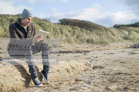 Young man using digital tablet, Brean Sands, Somerset, England