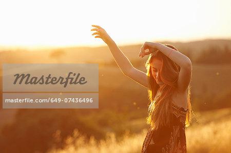 Teenager dancing in field at dusk
