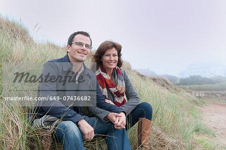 Couple watching from sand dune, Thurlestone, Devon, UK