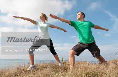 Mid adult couple exercising on cliff top, Thurlestone, Devon, UK