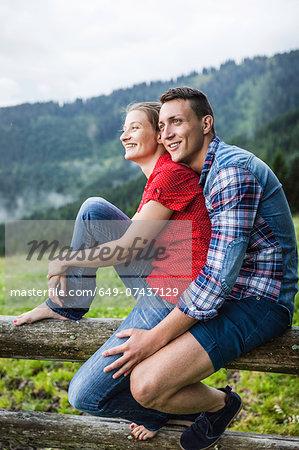 Portrait of couple sitting on fence, Tyrol Austria