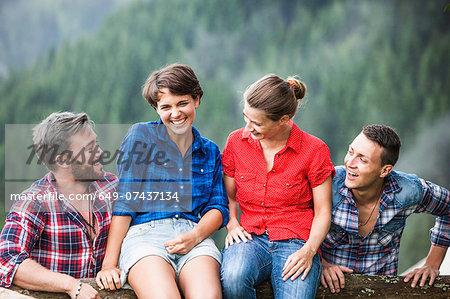 Two couple sitting on fence, Tyrol Austria