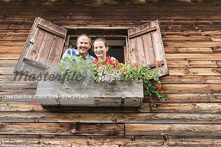 Portrait of couple at chalet window, Achenkirch,  Tyrol, Austria