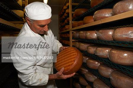 Senior man checking cheese round at farm factory