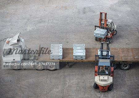 High angle view of fork lift trucks  loading alloy ingots onto transport
