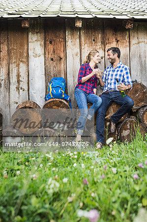 Couple sitting on cut logs having wine