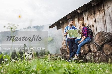 Couple with map discussing their trek, Tirol, Austria